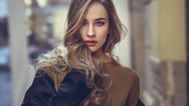 Blonde woman in urban background. Beautiful young girl wearing black leather jacket and mini skirt standing in the street. Pretty russian female with long wavy hair hairstyle and blue eyes.